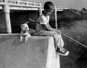 A boy and his dog crappie fishing.